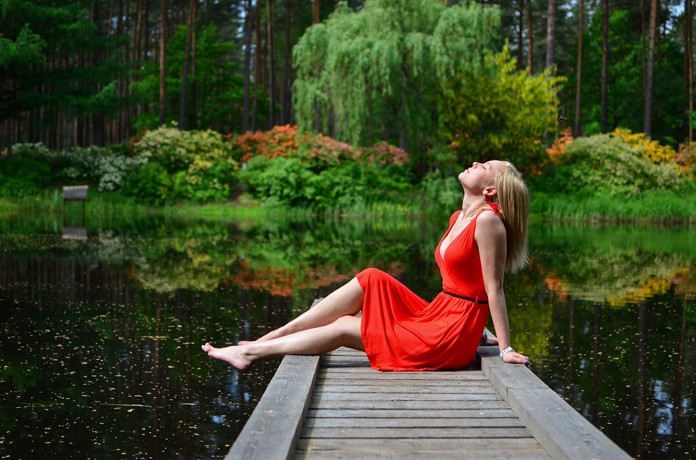 woman in red dress sitting on a pier above a lake, creating affirmations