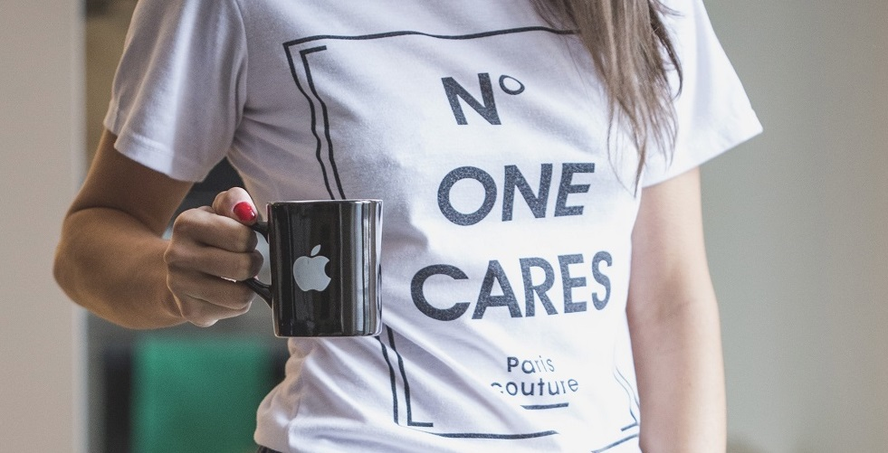 woman with apple coffee mug and wearing a t-shirt that says n o one cares, showing the power of self care first