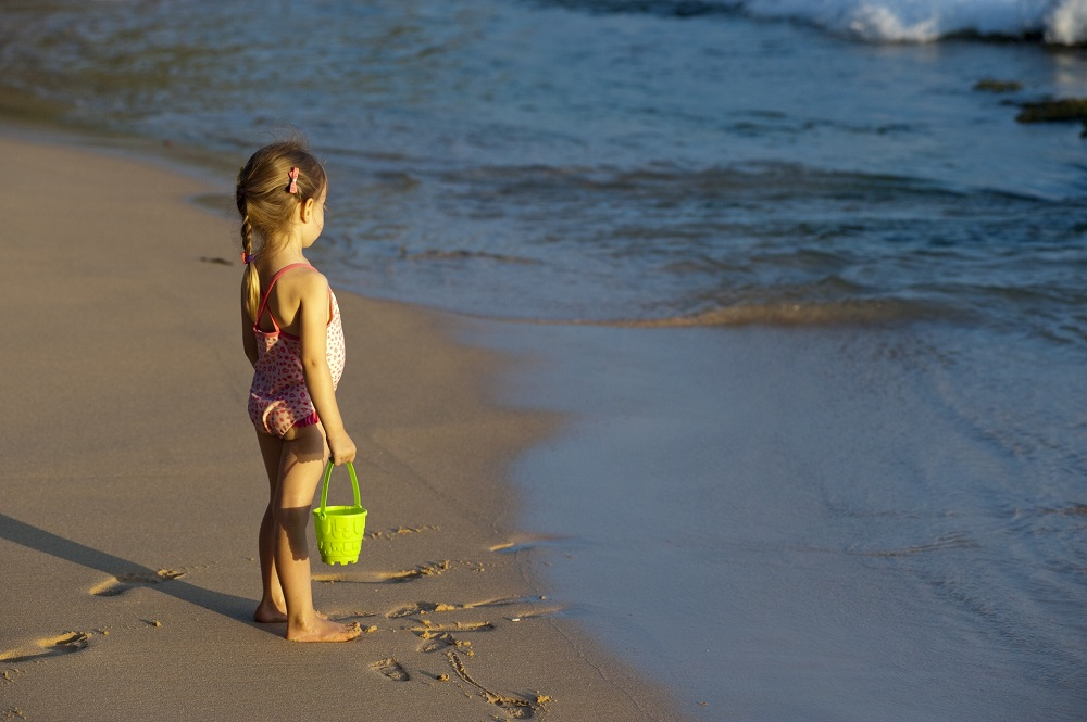 little girl is playing in the sand on the ocean, symbolizing the difficulties of setting boundaries