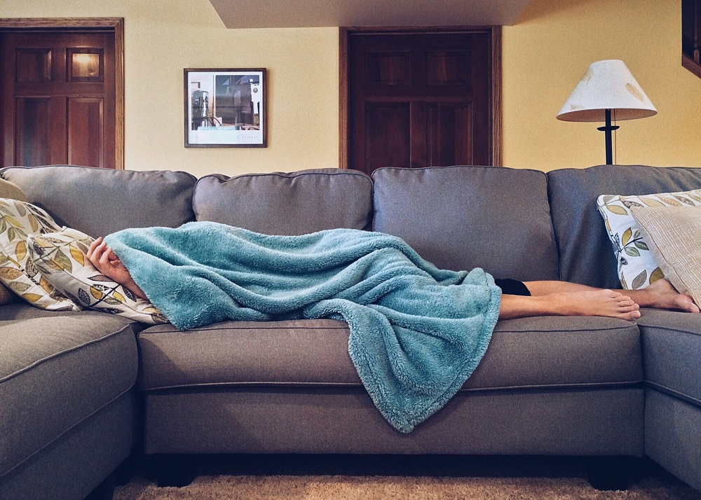 woman laying on the sofa, having a blanket hold over her head, stop judging yourself and start loving yourself first
