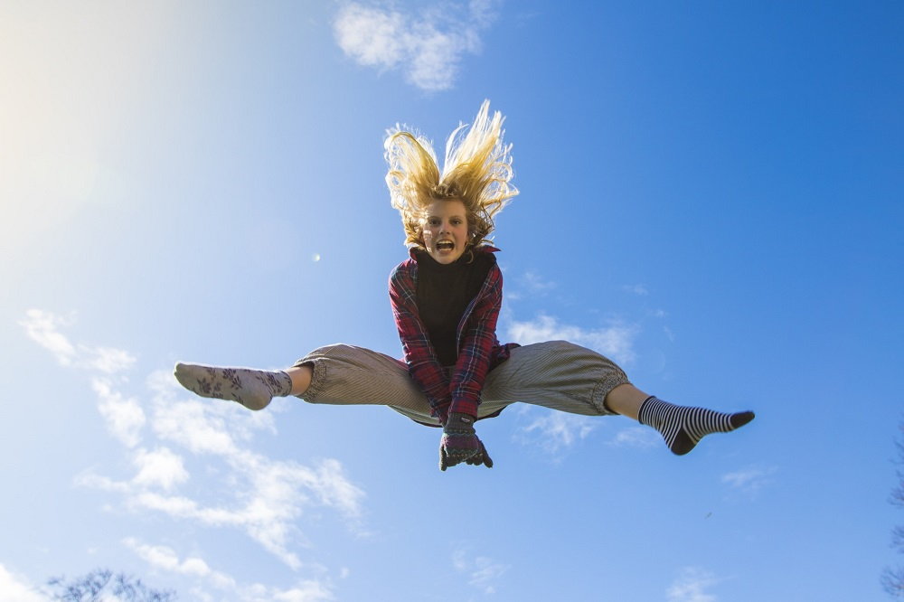 woman in winter cloth and socks jumping in the air with blue sky behind her, symbolizing the power of being present
