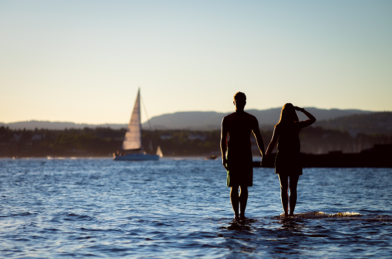 two people standing on the ocean, holding hands and watching a sailboat, having good relationship rules