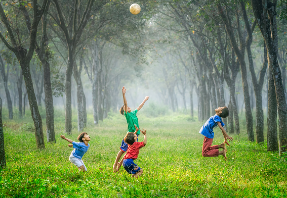 boys playing with a ball in the grass in the middle of trees, inner child healing