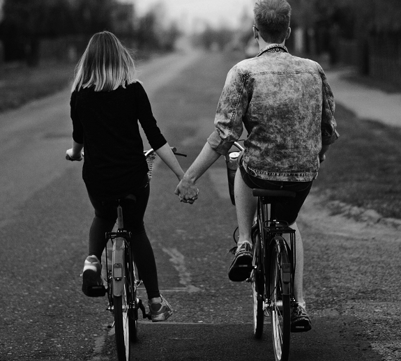 a couple holding hands while riding their bikes, symbolizing good relationship rules