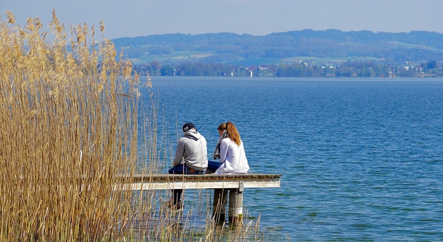 a couple sitting on a pier on a lake, keep peace with your spouse when you are upset