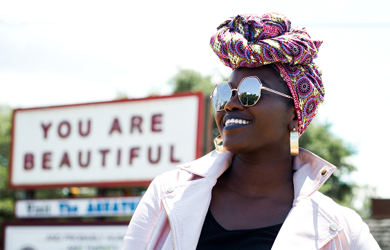 an African American woman in front of a sign You Are Beautiful, inner child healing