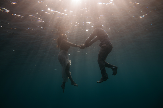 a couple dressed swimming in the ocean and holding hands underneath the water, good relationship rules