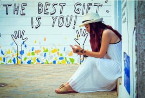 woman sitting in front of a wall painting, the best gift is you, symbolizing how to be a better mom