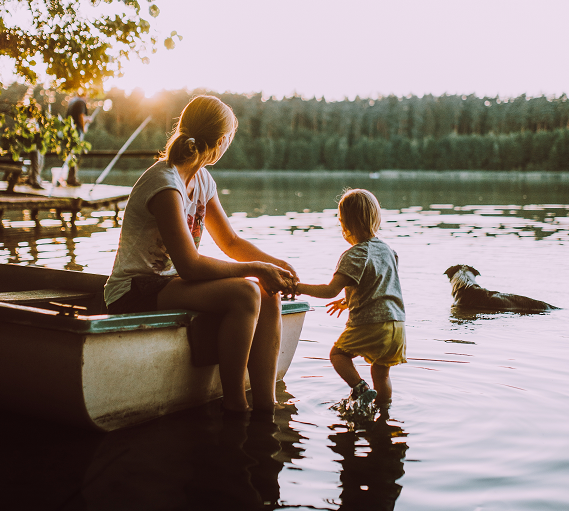 a mom holding its child's hand, sitting in a boat on the lake edge, symbolizing how to be a better mom